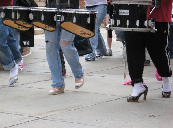 Close up image of drummers in women's high-heel shoes.
