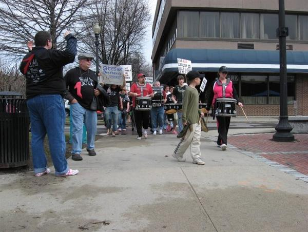 Image of drumline and walkers marching down the sidewalk in women's high-heel shoes.